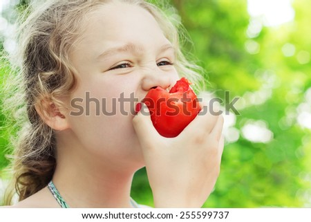 Closeup little girl is eating ripe tomato outdoors, freshness and healthy food concept - stock photo