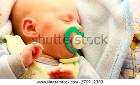 Closeup little newborn baby girl 24 days sleeping with dummy in mouth - stock photo