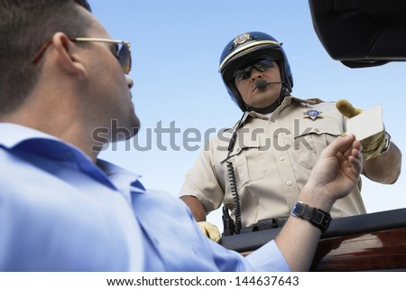 Closeup low angle view of a man handing license to police officer against clear blue sky - stock photo
