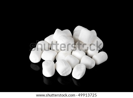 closeup macro of a small group of white mini marshmallows on a black plate - stock photo