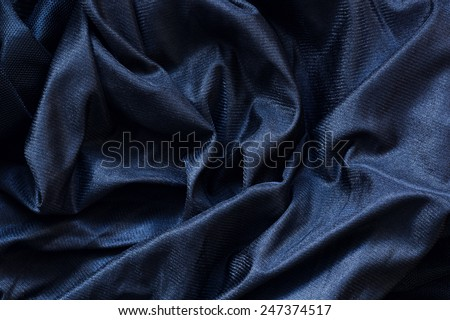 Closeup macro texture of black shiny smooth material fabric, clothing background with wrinkles and folds - stock photo