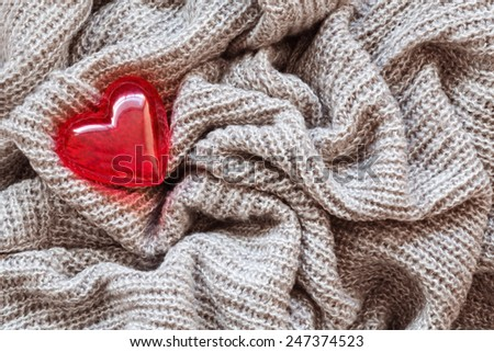 Closeup macro texture of knitted wool fabric material with lonely red shiny smooth heart on top, clothing background with wrinkles and folds, Valentine holiday love card - stock photo