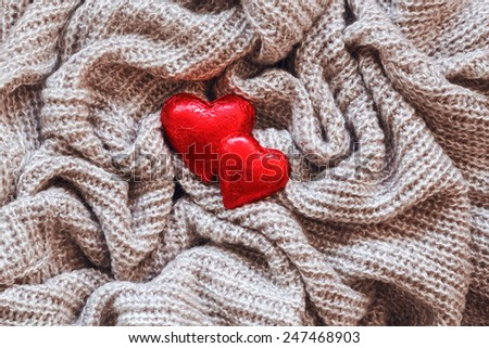 Closeup macro texture of knitted wool fabric material with red candy hearts on top, clothing background with wrinkles and folds, Valentine holiday card, love concept - stock photo