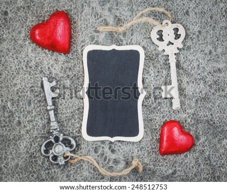 Closeup macro texture of knitted wool grey shawl with two red hearts, victorian keys and wooden plate board plaque with copyspace for text, Valentine holiday card, love romance vintage concept  - stock photo