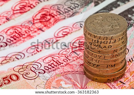 Closeup macro view at UK currency fifty pound banknotes and stack of one pound coins  - stock photo