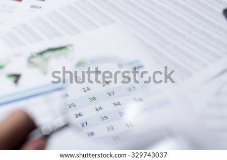 Closeup magnifying glass over paper with numbers and calculator sitting besides. - stock photo