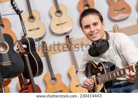 Closeup man playing a guitar and recording her music in computer - stock photo