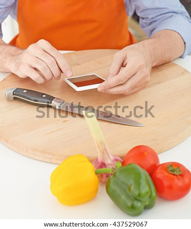 Closeup man's hands  pointing finger on smartphone before cutting vegetables on a work surface in a kitchen. cooking, technology and home concept  - stock photo