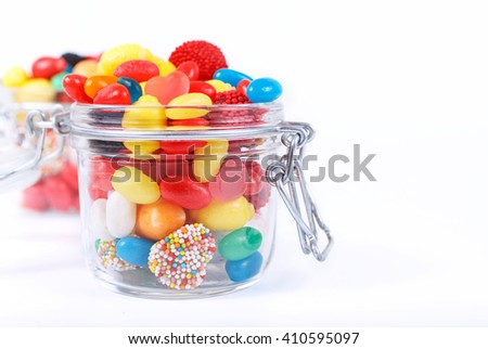 Closeup many different colorful candies and chewing gum in the glass jar on a white background with space for your text - stock photo