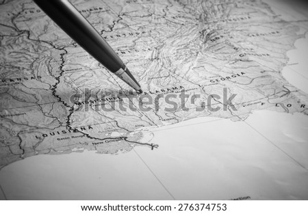 closeup map of Alabama and pen pointing to destination for trave - stock photo