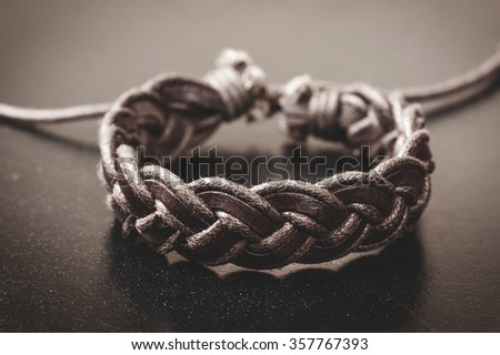 closeup men's leather bracelet with filtered - stock photo