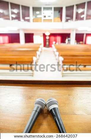 Closeup microphone in empty church with empty pews - stock photo