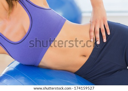Closeup mid section of a fit woman exercising with fitness ball at a gym - stock photo