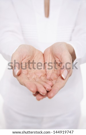 Closeup midsection of a woman cupping her hands against white background - stock photo