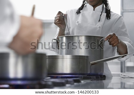 Closeup midsection of chefs cooking in the kitchen - stock photo