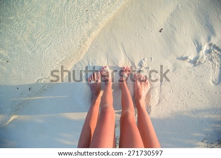 Closeup mother and kid feet on white sand beach - stock photo