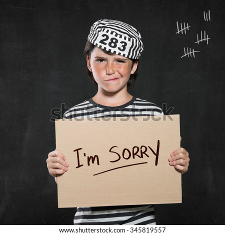 Closeup mugshot photo of boy holding I'm sorry sign. Young boy make a face wearing jail suit isolated on black background. Little contrite scamp showing his remorse. - stock photo