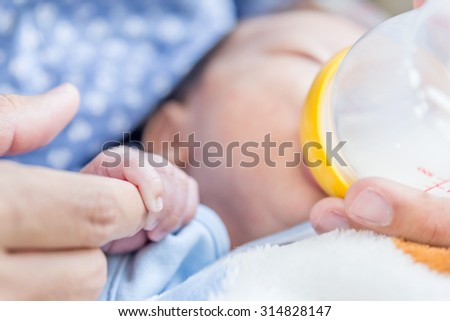 Closeup newborn baby holding father's hand and drinking milk from a baby bottle  - stock photo