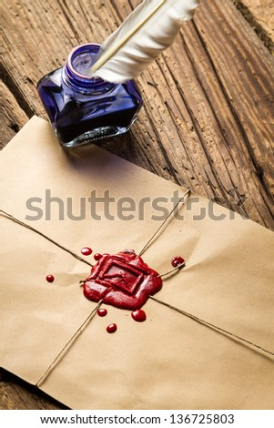 Closeup o blue ink inkwell on envelope with red sealant - stock photo