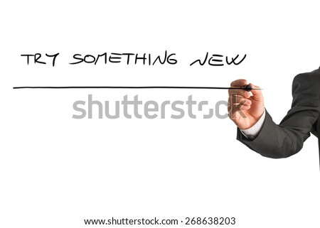 Closeup od male hand writing a motivational message Try something new from behind a white virtual screen in order to motivate you to never stop exploring and challenging yourself. - stock photo