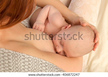 Closeup of a baby of 7 weeks old being breastfed - stock photo