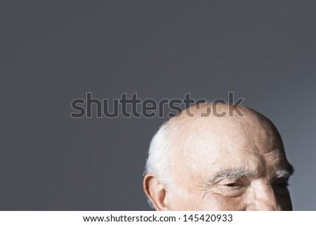 Closeup of a balding senior man against gray background - stock photo