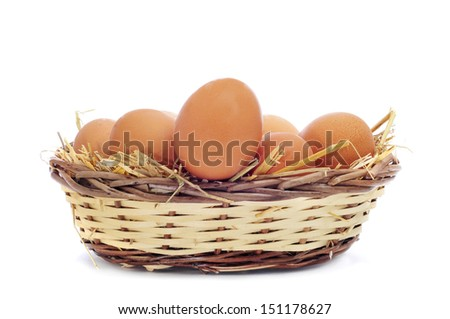 closeup of a basket with straw and a pile of brown eggs, on a white background - stock photo