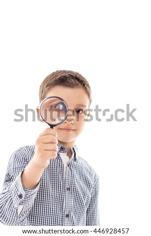 Closeup of a beautiful child looking through a magnifying glass loop over white background - stock photo