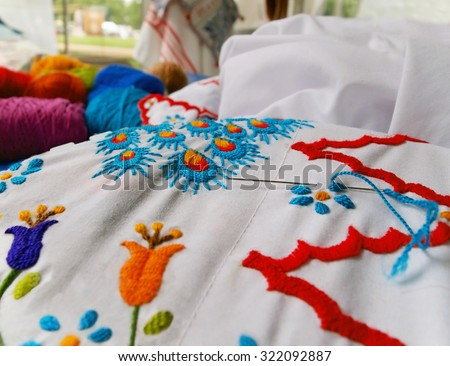 Closeup of a beautiful floral embroidery project with multiple colors of embroidery thread and a needle on white cloth. - stock photo