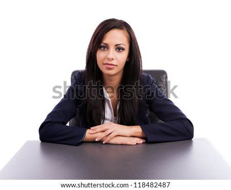 Closeup of a beautiful latin businesswoman sitting at desk isolated on white background - stock photo