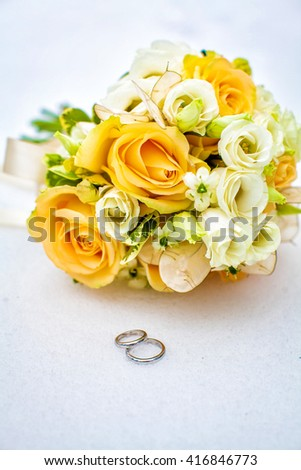 Closeup of a beautiful wedding bouquet of yellow roses, tied with ribbon for bride close wedding rings. White background. - stock photo