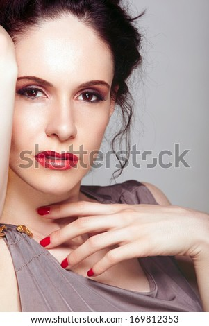Closeup of a beautiful woman's face with red nailpolish on her hand and pink eyeshadows - stock photo
