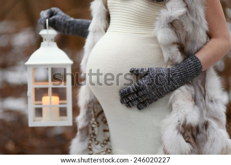 Closeup of a belly of pregnant woman holding lantern - stock photo