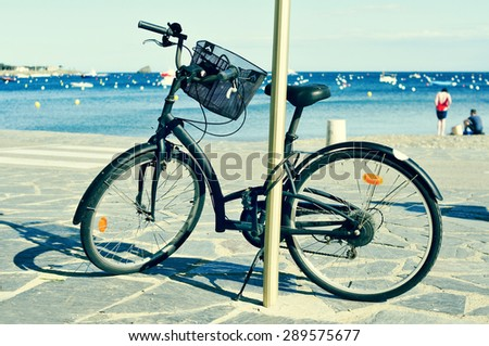 closeup of a bicycle parked in a seafront on the Mediterranean sea with blurred people on the seashore in the background, with a filter effect - stock photo