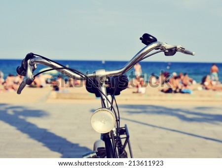 closeup of a bicycle parked on the seafront with people on the beach in the background, with a filter effect - stock photo