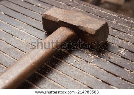Closeup of a big hammer on iron table with wooden dust - stock photo