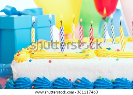 Closeup of a birthday cake with burning candles - stock photo