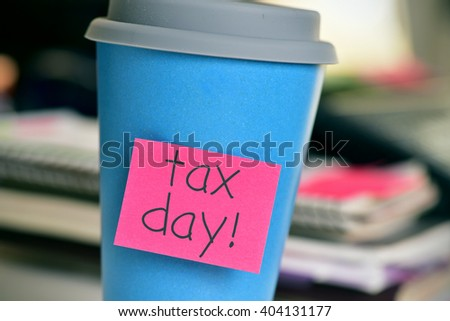 closeup of a blue coffee cup with red sticky note attached to it with the text tax day, in the office - stock photo