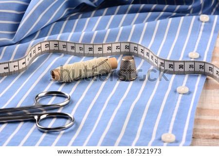 Closeup of a blue striped mens dress shirt ready for tailoring with scissors, thread, needle thimble and tape measure. Horizontal format filling the frame. - stock photo