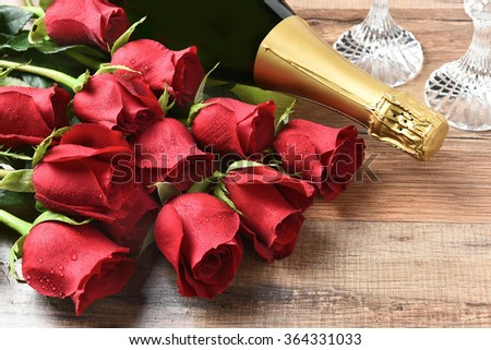 Closeup of a bottle of champagne and red roses on a wood table. Valentines Day / Love concept. - stock photo
