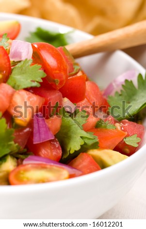 Closeup of a bowl with fresh cherry tomatoes and avocado salsa. - stock photo