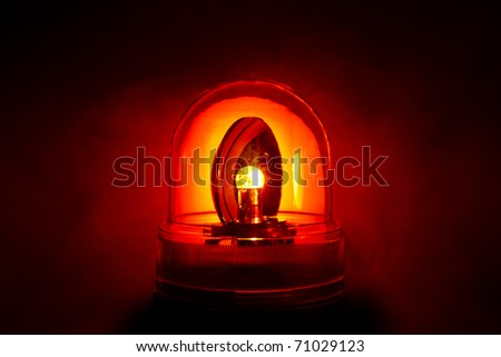 Closeup of a bright red police light shot through a smoky night - stock photo