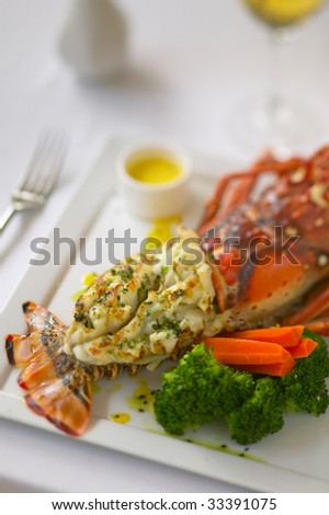 Closeup of a broiled or baked lobster tail with vegetables. - stock photo