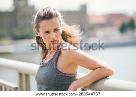 Closeup of a brunette jogger looking over her shoulder as she is resting on a bridge and looking over her shoulder while listening to music. - stock photo