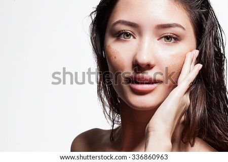 Closeup of a brunette woman making a face peeling scrub on a white background isolated - stock photo