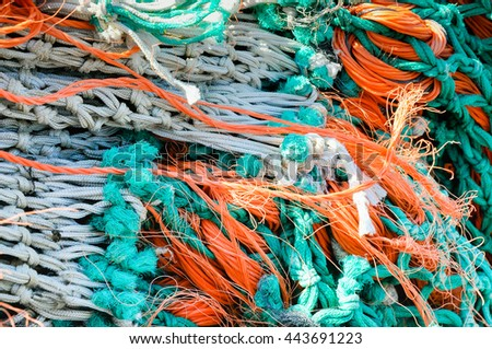 Closeup of a bunch of colorful knotted fishing nets, ropes and lines on the dock of a Dutch fishing port on a sunny day in spring. - stock photo