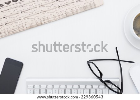 closeup of a business desk consisting on a financial newspaper, keyboard, mobile phone, wireless mouse, reading glasses and a cup of coffee - stock photo