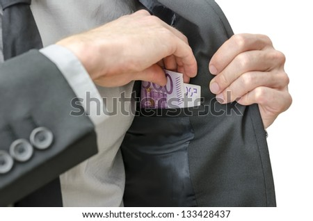 Closeup of a business man in suit putting banknotes in his jacket pocket. - stock photo