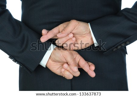 Closeup of a business man with his hands behind his back and fingers crossed. Torso and hands only, man is unrecognizable. - stock photo