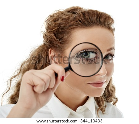 Closeup of a business woman looking at camera through a magnifier - stock photo